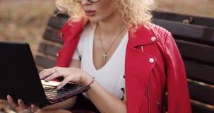 Pomy?lna blondynki kobieta pisa? na maszynie na laptopie w parku w jaskrawej przypadkowej kurtce zbiory