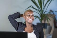 Pomyślna czarna afro Amerykańska biznesowa kobieta pracuje przy nowożytny biurowy uśmiecha się rozochocony opierać relaksuję na k Zdjęcia Stock