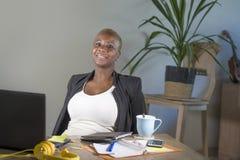 Pomyślna czarna afro Amerykańska biznesowa kobieta pracuje przy nowożytny biurowy uśmiecha się rozochocony opierać relaksuję na k Zdjęcie Royalty Free