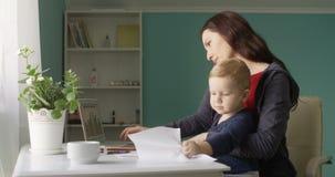 Pomyślna matka Pracuje od ministerstwo spraw wewnętrznych z dziecko synem Bałagani w górę stołu z papierami i dokumentami przy zbiory wideo