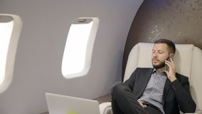 Pomyślna przedsiębiorca osoba opowiada na telefonu obsiadaniu w pierwszej klasie samolotowy przedsiębiorca zbiory