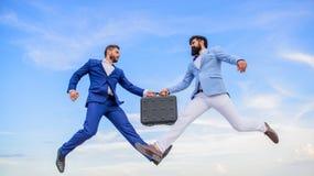 Pomyślna transakcja między biznesmenami Łatwy dylowy biznes Biznesmeni skaczą komarnicy w połowie powietrze podczas gdy chwyt tec obraz royalty free