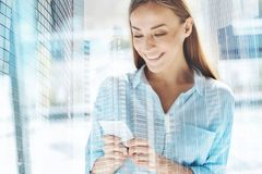 Pomyślna uśmiechnięta kobieta używa telefon komórkowego zdjęcia royalty free