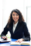 Pomyślna biznesowa kobieta przy biurowym miejscem pracy z laptopem & książką Obrazy Stock