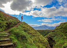 Pomyślna wycieczkowicz kobieta stoi samotnie w dzikiego na halnym wierzchołku i patrzeje nowi sceniczni, breathtaking miejsce prz fotografia stock
