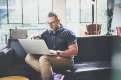 Pomyślnego kierownika laptopu Nowożytnego projekta Loft Pracujący Wewnętrzny studio Obsługuje Siedzącą rocznik kanapę, Używa wspó Zdjęcie Stock