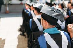 Pomyślni absolwenci w akademickich sukniach przy skalowaniem, siedzi zdjęcie royalty free