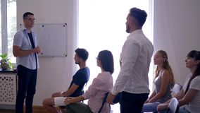 Pomyślni ludzie przy szkoleniem, mówca słuchają młody faceta kolega o rozwoju biznesowi pomysły w pokoju zbiory