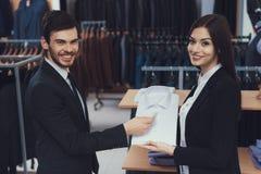 Pomyślni młodzi biznesmenów spojrzenia przy koszula który pokazuje w biznesu stylu sklepie odzieżowym konsultant zdjęcia stock