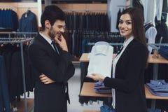 Pomyślni młodzi biznesmenów spojrzenia przy koszula który pokazuje w biznesu stylu sklepie odzieżowym konsultant zdjęcie stock