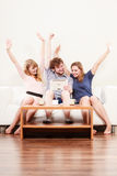 Pomyślni szczęśliwi przyjaciele z pastylką w domu Zdjęcia Royalty Free