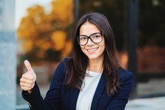 Pomyślny ładny kobiety spojrzenie kamera i pokazywać kciuk w górę znaka na budynku biurowego tle Fachowa kobieta zdjęcia royalty free
