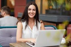 Pomyślny żeński freelancer pracuje daleko na laptopie, siedzi w plenerowej kawiarni, przyjemnego uśmiech, cieszy się daleką pracę zdjęcia stock