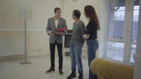 Pomyślny agent nieruchomości pokazuje młodej ślicznej parze małżeńskiej nowego dom Szczęśliwy mężczyzna i kobieta patrzeje wokoło zbiory