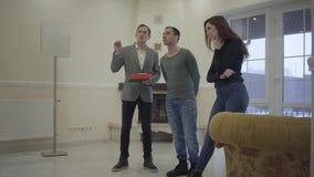 Pomyślny agent nieruchomości pokazuje młodej parze małżeńskiej nowego dom Szczęśliwy mężczyzna i kobieta patrzeje wokoło dzierżaw zbiory