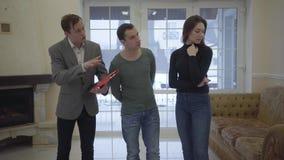Pomyślny agent nieruchomości pokazuje młodej ufnej ślicznej parze małżeńskiej nowego dom Szczęśliwy mężczyzna i kobieta patrzeje  zdjęcie wideo