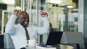 Pomyślny amerykanina afrykańskiego pochodzenia biznesmen używa laptop otrzymywa dobrą wiadomość i zostać bardzo szczęśliwy i z po zbiory