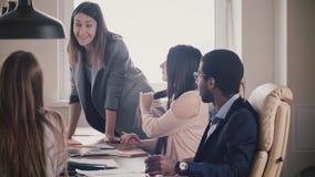 Pomyślny atrakcyjny bizneswoman zachęca wieloetnicznej drużyny Młodego żeńskiego szefa wiodący biurowy spotkanie stołem zbiory