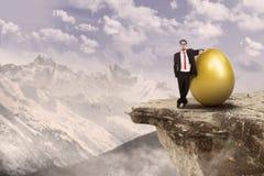 Pomyślny biznesmen i złota jajko Fotografia Royalty Free