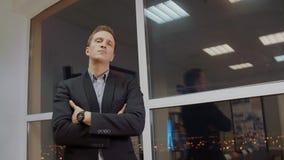 Pomyślny biznesmen w klasycznej formalnej kostium pozycji w wieczór biurze z rękami krzyżował na klatce piersiowej blisko okno zdjęcie wideo