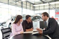 Pomyślny biznesmen w przedstawicielstwie firmy samochodowej - sprzedaż pojazdy obrazy stock
