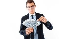 Pomyślny biznesmen w szkłach i kostiumu, trzyma dolarowy b fotografia royalty free