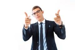 Pomyślny biznesmen w szkłach wskazuje, ono uśmiecha się radośnie, fotografia royalty free
