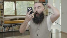Pomyślny biznesowy mężczyzna dostaje wielką wiadomość na mądrze telefonie i wyraża reakcję z rękami szczęścia i omg - zdjęcie wideo