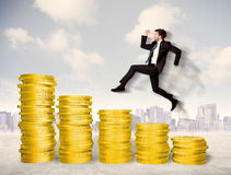 Pomyślny biznesowy mężczyzna skacze up na złocistej monety pieniądze Zdjęcia Stock