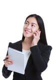 Pomyślny bizneswoman opowiada na telefonie i trzyma notatkę p Obrazy Royalty Free