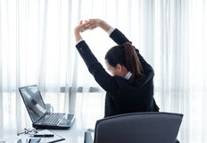 Pomyślny bizneswoman relaksuje w jej krześle przy biurem Zdjęcie Stock