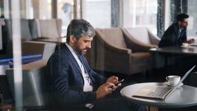 Pomyślny kierownik używa smartphone podczas przerwy na lunch w nowożytnej kawiarni zdjęcie wideo