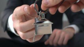 Pomyślny mężczyzna daje pieniądze pośrednik handlu nieruchomościami, bierze kluczowego nowego dom, zakup i czynsz, zdjęcie wideo