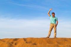 Pomyślny mężczyzna macha rękę od diuna wierzchołka w pustyni Zdjęcia Royalty Free