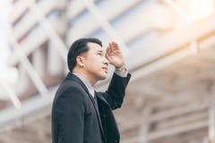 pomyślny mężczyzna przedsiębiorca przyglądający up na nowożytnym drapaczu chmur podczas gdy stojący outdoors, młody wykonawczy mę Zdjęcie Stock
