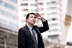 pomyślny mężczyzna przedsiębiorca przyglądający up na nowożytnym drapaczu chmur podczas gdy stojący outdoors, młody wykonawczy mę Obrazy Royalty Free