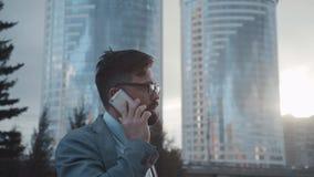 Pomyślny mężczyzna w kostiumu chodzi puszek i opowiada na telefonie ulica zbiory wideo