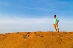 Pomyślny mężczyzna z brodą w koszulki błękitnych kosztach przy wydmowym barkhan wierzchołkiem w pustyni Przy backgr Obrazy Royalty Free