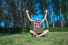 Pomyślny mężczyzna z laptopu outoor pracującym obsiadaniem na trawie obraz stock