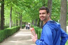 Pomyślny męski biegacz trzyma bidon w parku z kopii przestrzenią z słuchawkami Zdjęcie Royalty Free