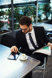 Pomyślny młodego człowieka obsiadanie na tarasie restauracja i robi planom dla dnia Fotografia Royalty Free