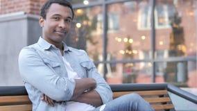 Pomyślny młody afrykański mężczyzny obsiadanie na ławce zbiory wideo
