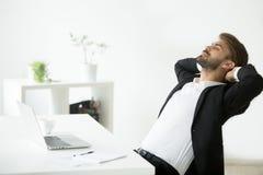 Pomyślny młody biznesmen relaksuje przy miejsca pracy breat w kostiumu Zdjęcia Royalty Free