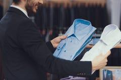 Pomyślny młody biznesmen w kostiumu wybiera koszula kupować Butik garnitury obrazy stock