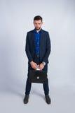 Pomyślny młody biznesmen z telefonem i teczką Fotografia Stock
