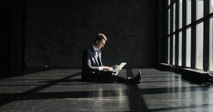 Pomyślny młody człowiek Pracuje W ministerstwie spraw wewnętrznych w loft stylu Elegancki modnisia mężczyzna w kostiumu pracuje p zbiory