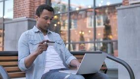 Pomyślny Online zakupy Afrykańskim mężczyzny obsiadaniem na ławce zbiory