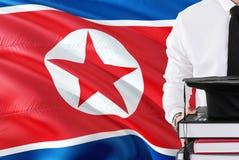 Pomyślny Północno-koreański studencki edukacji pojęcie Trzymający książki i skalowanie nakrętkę nad koreą północną zaznacza tło zdjęcie stock