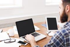 Pomyślny przypadkowy biznesmen pracuje z laptopem i pastylką w biurze, zamyka up Zdjęcia Stock