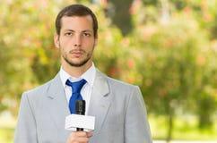 Pomyślny przystojny męski wiadomość reportera być ubranym Zdjęcia Stock